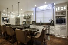 Comfortable, yet luxurious kitchen design with two-tiered kitchen island with very comfortable seating. The dark island is offset with white cabinetry throughout the rest of the kitchen. Grand Kitchen, Kitchen On A Budget, Kitchen Ideas, Rustic Kitchen, Kitchen Inspiration, Kitchen Decor, Kitchen Designs Photos, Best Kitchen Designs, Kitchen Pictures