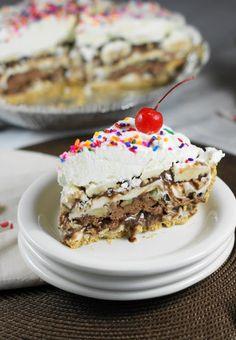 Amazingly delicious Frozen 7-Layer Banana Split Pie, complete with homemade chocolate sauce.  A super tasty ice cream treat!   www.thekitchenismyplayground.com
