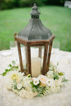 Rustic lanterns resting in lush floral wreaths make for lovely centerpieces at a wedding at the Inn at Perry Cabin. Planning and Design by Pineapple Productions. Photo by Jacqueline Campbell. Floral Design by Dragonfly Events.