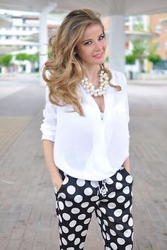 Black and white polka dot pants with white sheer blouse and a bold pearl necklace