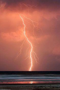 Lightning strikes over the Atlantic Ocean at sunset