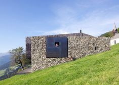 An enormous frame surrounds a little window in the reconstructed stone wall that flanks this holiday home in northern Italy