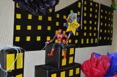 edificios de super heroes con cajas recicladas, el fondo es una ciudad de noche en papel marbeta de color negro y amarillo.