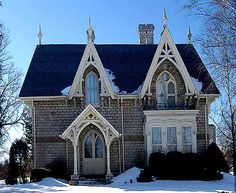Madoc    This house in Madoc has beautifully detailed gables which echo the lancet arch of the window. The woodworking on the front porch is a masterpiece of design, the structural members are firmly stated, there is a quatrefoil in the center, and, again, the lancet arch is echoed. The finials popping up above the roof give the building a distinctive silhouette.