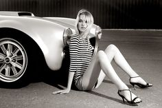 This photo is full of smooth, clean lines. From the shape of the car, to the stripes in the model's clothes all the way down to the way she has her legs propped up.