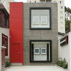 Placa cimentícia Eternit para mais rapidez e facilidade na fachada da loja Moldura Minuto. São Paulo. Projeto NK Arquitetura. Fachada em concreto, com acabamento em preto nas janelas e faixa e porta vermelha.