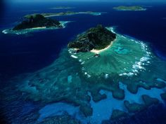 Fiji Islands  Photograph by James Stanfield  A dramatic collar of coral reefs rings Mondriki Island, foreground, and Monu Island, background, two of Melanesia's Fiji Islands. The Fiji Islands are made up of 333 islands in the South Pacific, known for their sparkling beaches, coral gardens, and lush rain forests.