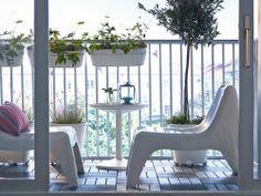 Een balkon met plastic loungestoelen een rond salontafeltje en hangende planten