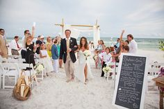 Bamboo arbor with white sheer fabric accents.  The perfect, romantic beach wedding with a chalkboard program and parasols for guests to use.  Decor and flowers designed by Bella Flora 30a