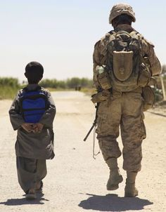 Soldier walking boy safely to school with new school supplies donated by US military