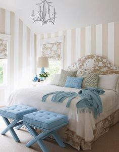 Tan & turquoise blue chic bedroom design with Adler tufted velvet X-Bench, light blue pagoda chandelier, beige white toile fabric roman shades, blue gourd lamps, blue cashmere throw blanket, blue gray animal print pillows, beige white tolie upholstered headboard and bedskirt and beige rug carpet. white beige blue gray bedroom colors