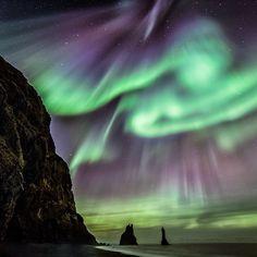 Auroras dançam sobre trolls petrificados na praia de Vik í Myrdal, Islândia. Autorae dance over petrified trolls at the Vik í Myrdal…