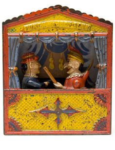 """Punch and Judy Mechanical Bank »    Circa 1884: This bank represents a typical Punch and Judy theatre, scenery, curtain and all. Judy receives the coin in a plate in her hand, a lever is pressed and Punch rushes forward brandishing a club, when Judy turns quickly and deposits the coin in the bank. Name """"Punch and Judy Bank"""" above the stage opening"""