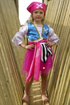 This fantastic girls pirate costume comes complete with a pink cross bone head scarf. The Pirates dress has a lace edged satin shirt with a turquoise, gold brogue edged waist coat. The pink net skirt is lined with satin and has a stripy apron #dressingupoutfits #childrensfancydress #fancydress #pirate #pirateparty
