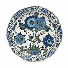 AN IMPORTANT 'DAMASCUS-STYLE' IZNIK POTTERY DISH - ATTRIBUTABLE TO THE 'MASTER OF THE HYACINTHS', OTTOMAN TURKEY, CIRCA 1555 - With cusped sloping rim on short foot, the white ground painted in cobalt-blue, turquoise, sage-green, manganese & grey with a bold floral spray composed of two large flowerheads issuing from a leafy frond, branches of hyacinth blossom & curved saz leaves in a near-symmetrical arrangement, the rim with a stylised 'wave & rock' design, 14in diam.