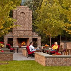 Brick fireplace patio with low brick walls capped with stone.   via houzz