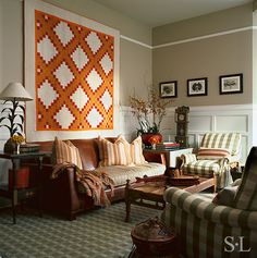 A Double Irish Chain quilt in cheddar and red hangs on the living room wall - Suzanne Lovell Inc.
