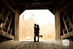 Romantic silhouette photo from Engagement Session at covered bridge in Tyler State Park © Angelina M. Photography, LLC