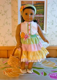 Our American Girl is going out to the sunny, spring garden to look for Easter eggs and maybe pick some flowers for the hall table. She looks like a spring flower herself, in this beautiful gingham dress and hairband. The dress bodice is lined. It has pink gingham trim at the neck and armholes. There is a gingham tab at the front decorated with green rickrack and double buttons. It closes in back with three buttons and hand-sewn button loops. The skirt has three pastel gingham tiers in green…