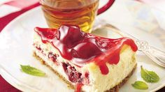 Dazzle guests with a crowd-sized cheesecake bursting with swirls of ruby red fruit.