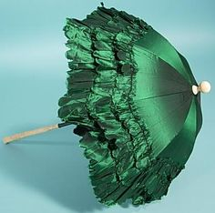 Emerald green silk parasol with scalloped ruffles on carved bone folding handle, late 1880s
