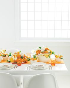 An all-white table setting gets an orange punch of color with bowls and platters filled with navel oranges, clementines, and kumquats.