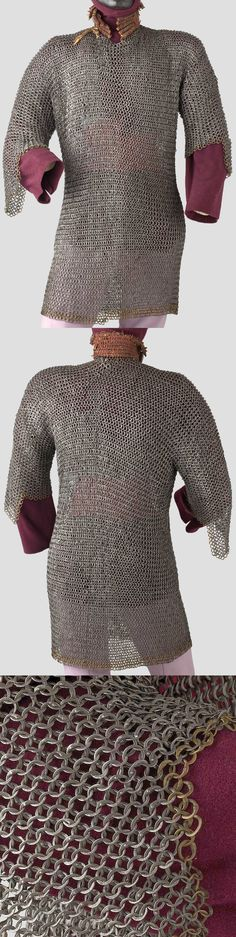 European (German) riveted mail hauberk, 15th century. Hip-length with semi-long arms, short overlapped neck with braid collar (a later addition). Alternating rows of riveted and solid rings, the diameter of the rings on the sides a little smaller. The hem and sleeve edges decorated with rows of brass rings. Extremely rare, early chain shirt in almost undamaged condition (small defect of three rings on the right shoulder). Length of 78.5 cm.