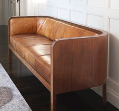 I really like the curved wooden frame of this sofa and the Smokey tan leather. Beautiful.