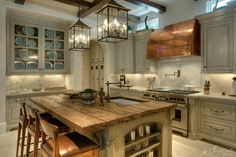 Beautiful kitchen - cool lights and rustic island. love the tones.