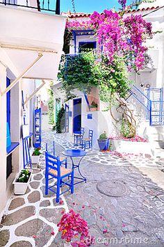Pueblo tradicional griego típico en verano con las paredes blancas, los muebles azules y el bougainvilla colorido, isla de Skiatho