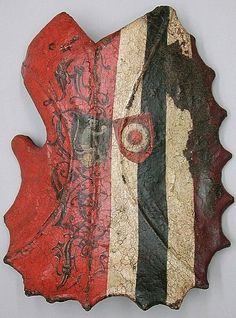 """Tournament or Cavalry Shield (Targe), ca. 1450–1500, German (Nuremberg) -- """"The surface displays two campaigns of painting. The earlier decoration shows a vertically divided design: on the left, red with letters AGVF, probably those of the shield's owner, and on the right colored stripes. Over them are two small shields displaying the arms of Lucas Ketzel (on a black ground a silver monkey holding a gold ball) and Magdalena Koller (on a red ground a silver ring), married in 1467."""""""