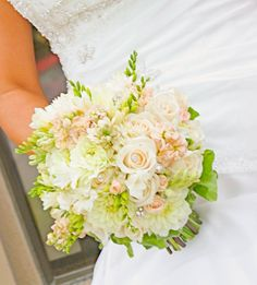 The bridal bouquet will be a clutch of cream hydrangeas, white freesia with green tips, peach roses, ivory stock, and green hypericum berries wrapped in white ribbon.