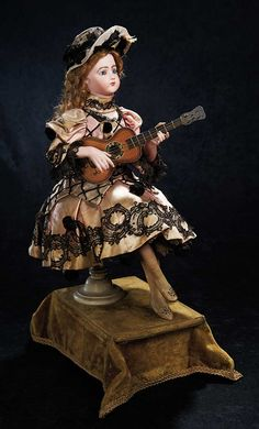 "Theriault's. Stunning all original French bisque Automaton ""Spanish Lady with Guitar"" by Leopold Lambert. As music plays she elegantly turns her head, nods, taps her foot, and strums her wooden decorated guitar with her right hand. This rare automaton is wearing her original rose satin costume with black pom poms and lace. Circa 1890. Upcoming at Theriault's Stein am Rhein auction on March 29th and 30th, 2014 in Naples Florida.   For more info please visit: http://www.theriaults.com/"