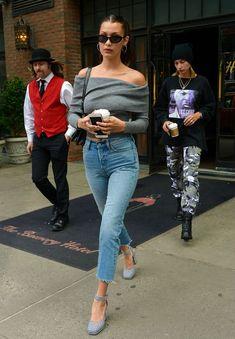 10 looks para copiar de Bella Hadid. Blusa cinza de manga com babado e decote ombro a ombro, calça jeans cropped, sapato mary jane xadrez
