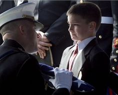 """Choking back tears, 8-year old Christian Golczynski accepted the flag from his father's casket. Photographer Aaron Thompson described this moment as """"the most emotionally moving event I may have ever witnessed and may ever witness in my life."""" (The Daily News Journal)  When asked about his dad by ABC News' Chris Cuomo, Christian said, """"He was a hero. He helped our country."""""""