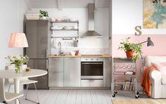 Cocina intima para loft individual. Color acero y acompañada por una bancada efecto madera natural.