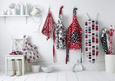 Prestigious Textiles -  Weekend Fabric Collection - Aprons with red and black spots, a black outline of butterflies and ladybugs, a white cloth with a modern floral pattern, and fabric handbag