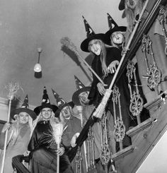 STAIRCASE OF WITCHES: A group of men in costume as witches, complete with brooms, to celebrate Halloween, lined the staircase of a house. c1950 photo by George Pickow/Getty Images