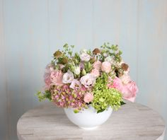 Delicate roses and blush lisianthus tucked in an airy bed of pink-green hydrangea: 'Blush Classic' by Winston Flowers.