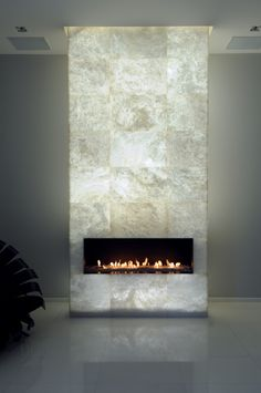 This bright backlit alabaster fireplace looks wonderful against the warm natural light of the flames. Part of Project Cheminée in Paris
