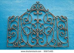 stock photo : A Decorative Piece of Wrought Iron Mounted to a Bright Colored Stucco Wall