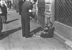 A Warsaw ghetto resident gives money to two children on a Warsaw ghetto street. Warsaw, Poland, between October 1940 and April 1943.