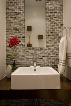"""The glass tile on the powder room wall has brown accents that complement the wenge counter that supports the """"trough"""" raised vanity. An object mirror hangs above and reflects the matching wenge floating display boxes on the wall above the toilet."""