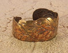 Three Leaf Bracelet is a one-of-a-kind bronze bracelet Artisan made in Chasing and Repousse. The leaves wrap around your wrist in a very comfortably fitted curve. This classic bronze bracelet is so comfortable and goes with just about any everyday outfit. - 1 3/8 wide. - Comfortable on a 7 to 7.5 wrist. - Signed Makers Card This convex easy-to-wear leaf design feels natural on the wrist, so it is comfortable even when you work on a computer all day. The bracelet was made exclusively with a…