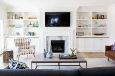 coastal beach style living room with white built-in shelves and cupboards around fireplace with tv above.