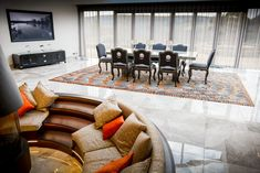 Orange, black and white printed rug in this contemporary dining room #contemporaryrug #rugpattern #brightrug