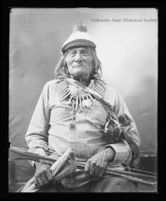 This black and white studio photograph shows Old Harney posing in front of a painted backdrop, sitting on a chair. He is wearing a striped shirt, long pants, moccasins, and a hat. He wears a bear claw necklace around his neck, and a bow is laid across his lap. The photograph was taken at the Rosebud Reservation. Date1900 circa Brule