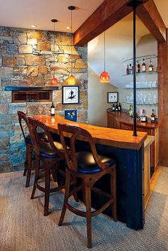 A slot window next to  the bar in the lower level offers a peek into an adjacent wine room, complete with room for 1,200 bottles. The stone used in the house came from Hot Springs, Montana.