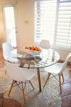 mesa redonda de vidro com cadeiras brancas