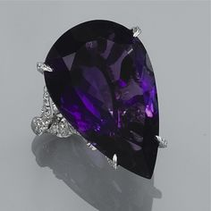 AN AMETHYST AND DIAMOND DRESS RING The claw-set pear-shape amethyst to pavé-set diamond ring mount